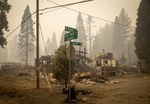 In this Sept. 15, 2020, file photo, scorched property stands at an intersection in Blue River, Ore., days after a blaze known as the Holiday Farm Fire swept through the area's business district.