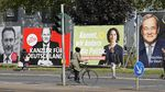 On Thursday, people in Gelsenkirchen, Germany, pass election posters of chancellor candidates Armin Laschet (from right) of the Christian Democratic Union, Annalena Baerbock of the Greens, Olaf Scholz of the Social Democratic Party and Christian Lindner of the Free Democratic Party.