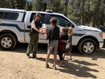 Laura Conard, a deputy with the Deschutes County Sheriff's Office, hands a box of free school meals to Shane, Peyton and Logan Smith (left to right, ages 12, 8 and 7, respectively) outside the Smiths' home near La Pine, Ore., on Monday, Aug. 31, 2020.