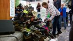People place shoes labeled with the name of someone lost to alcohol or drug addiction at a rally for recovery on Sept. 30, 2017.