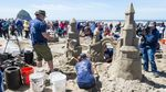 The Jessops work on their sandcastle as OPB — and the crowd— watches. Will their arches remain standing?