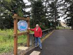 Florence, Ore., Mayor Joe Henry poses in front of the sign welcoming visitors to the Exploding Whale Memorial Park. The park is named in honor of the 1970 explosion of a rotting sperm whale on the Oregon Coast just outside of the city's limits.