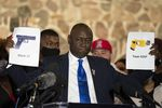 FILE - In this Thursday, April 15, 2021 file photo, attorney Ben Crump, representing the family of Daunte Wright, holds up images depicting an X26P Taser and a Glock 17 handgun during a news conference at New Salem Missionary Baptist Church in Minneapolis.
