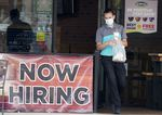 A customer wears a face mask as they carry their order past a now hiring sign at an eatery in Richardson, Texas.