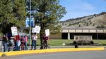 """A cluster of people holding picket signs stand on a sidewalk near a building with a sign out front that reads """"Oregon Institute of Technology."""""""