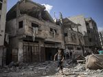 Palestinians inspect damaged houses that were hit in Israeli airstrikes in Gaza City early Monday.