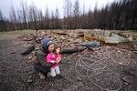 Lynne Piper and her daughter Ada, 4, play near the remains of their Elkhorn home, Feb. 26, 2021. The Piper family had only owned their 17-acre property in Elkhorn a short time before it was destroyed by the 2020 Santiam fire.