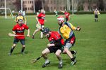Enda Grogan, center, spins in attempt to get by Scott Meyers, right, a Red Branch player dressed for the opposing side.