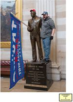 """A ma stands on the base of a statue in the US Capitol building. He has put a red """"Make American Great Again"""" on the statute, and a """"Trump"""" flag in the statue's hands."""