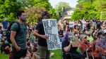 Attendees of the vigil for George Floyd hold up protest signs at Peninsula Park in Portland, Ore., Friday, May 29, 2020.