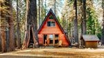 An A-frame house surrounded by large trees.