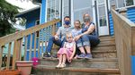 Rebecca Pierce, along with her husband and two daughters, sit on the front porch of the Astoria home.