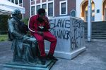 A local hip hop artist named Spazz sits on the Thomas Jefferson statue that was torn down from its pedestal at Jefferson High School in Northeast Portland