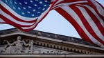 A US flag flies over a building with a carving of lady justice on its front.
