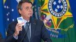 Brazilian President Jair Bolsonaro stands at a podium holding a box of medication.