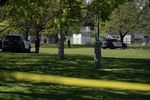 Two police cars and several officers are visible in a grassy park on a sunny day.