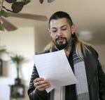 Leonardo Cruz looks over eviction paperwork at his home in Portland, Friday, Jan. 22, 2021.