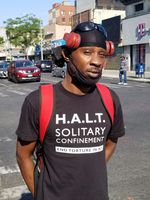 """A person wearing headphones with a face mask lowered below his chin looks at the camera. He wears a T-shirt with the words """"H.A.L.T. solitary confinement - end torture in NY"""""""
