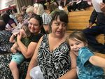 Julie Thompson (center) talks to her 4-year-old niece Charisma as they share bleacher seats with Charisma's mom, Merissa Biggs, and her 2-year-old brother Keeneye, Sunday, July 28, 2019. They were among 500 people who attended a community meeting on the fast-moving Milepost 97 Fire.