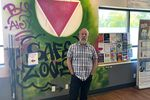 """A person stands with his hands in front of his pockets in front of a wall with graffiti-style art that includes a pink triangle and the words """"Safe zone"""""""