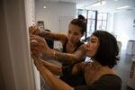 Bear Patton (left) and Taemi Izumi hang name placards for the Be Nice (White) You're In Bend exhibit at Scalehouse in Bend, Ore., on Aug. 6, 2021.