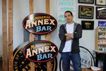 Nick Lee stands next to his latest project, a sign for McMenamins Annex Bar. Studio Signs Co. has been painting all of the signs for McMenamins.