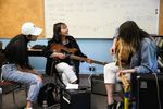 Tran Nguyen, center, smiles after writing a song with her band at the Pass the Mic workshop in Portland, Ore., Wednesday, July 31, 2019. The workshop connects experienced local musicians with immigrant and refugee youth.