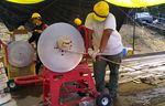 People wearing yellow hard hats crank great lengths of hose onto a spindle