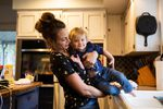 Emily Calabro lifts her daughter, Magnolia, 1, from the sink after dusting flour off her pants while baking at home in Vancouver, Wash., Thursday, April 2, 2020. Calabro and her husband, a firefighter, chose to send their daughter to stay with family in Kansas as fears grew about first responders' exposure to COVID-19.