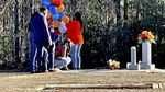 People holding colorful balloons stand together around a grave site, as one person kneels down and touches the ground.