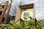 """A glass-walled academic building has a large yellow University of Oregon """"O"""" emblem emblazoned on its exterior."""