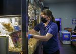 Theater assistant manager Jessica Freeman serves up a bag of popcorn at the Sandy Cinema in Sandy, Feb. 19, 2021. The theater is still closed for movie showings but sells concessions to go on weekends.