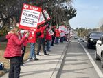 """People dressed in winter gear, all wearing red, stand in a line outside a hospital. They're holding up signs that read """"OFHNP Healthcare Workers On Strike Against Unfair Labor Practices,"""" as cars drive past."""