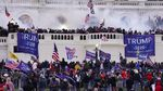 """Outside the US Capitol building people carry giant flags that read """"Trump 2020"""" and smaller US flags, while smoke drifts through the air."""