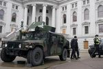 Police walk past armored vehicles outside the Wisconsin state capitol Sunday, Jan. 17, 2021, in Madison, Wis. Security has been increased around the capitol because of concerns that protests leading up to President-elect Joe Biden's inauguration could turn violent and destructive. (AP Photo/Morry Gash)