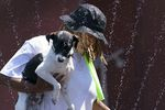 """Cultivate Initiatives co-director Y'Ishia Rosborough of Portland cools off with dog """"Hades"""" at a cooling station put on by Cultivate Initiatives at Sunrise Center in Portland, June 28, 2021. Currently the center plans to remain open until Wednesday at 9 AM."""