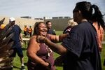 Mable Jackson (Modoc, Hupa) offers hugs and handshakes at the end of powwow at Two Rivers Correctional Institute in Umatilla, Ore., Aug. 24, 2019.